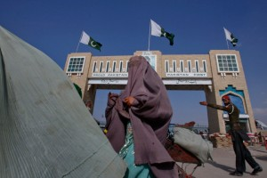 A policeman directs Pashtun women in burqa to the gates of the Pakistan-Afghanistan border crossing in Chaman November 27, 2011. Pakistan on Sunday buried 24 troops killed in a NATO cross-border air raid that has pushed a crisis in relations with the United States towards rupture.    REUTERS/Naseer Ahmed (PAKISTAN - Tags: CIVIL UNREST MILITARY)